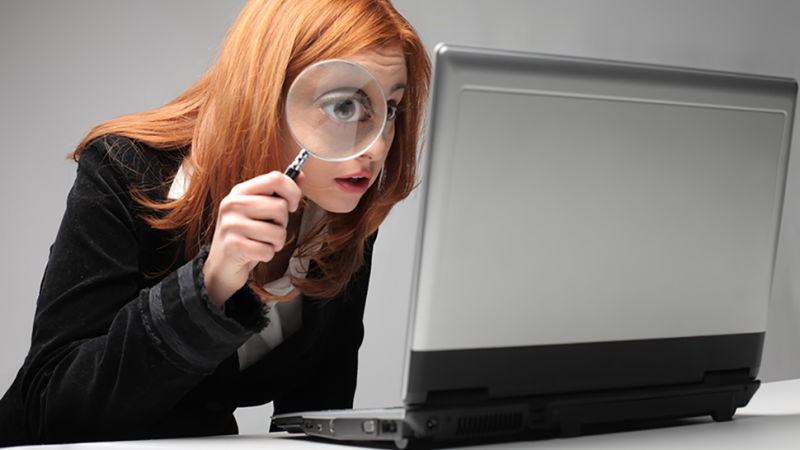 girl with a magnifying glass searching for a file on a laptop
